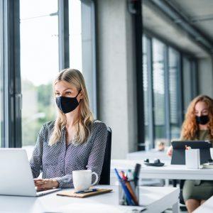 Pracownicy biurowi podczas pandemii COVID-19 w maseczkach ochronnych